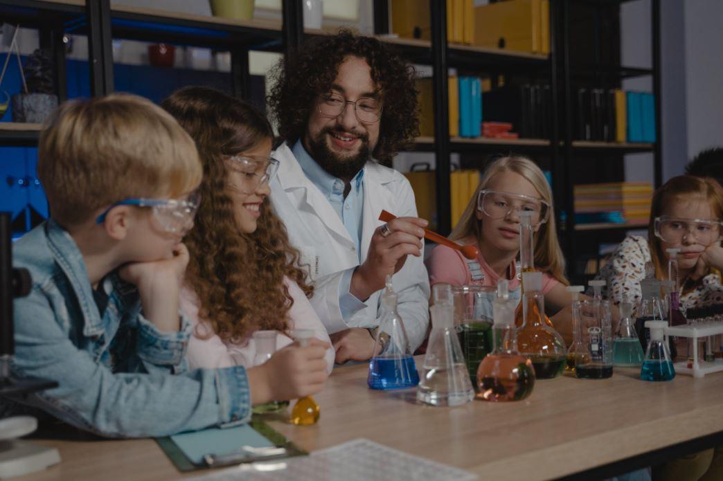Erwachsener Mann zeigt Kindern ein chemisches Experiment